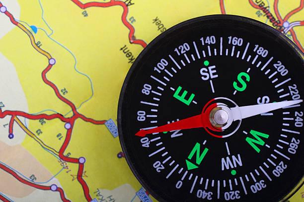 kompass auf der landkarte - kompass wanderkarte stock-fotos und bilder