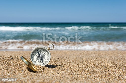 537607438istockphoto Compass on the beach 595725814