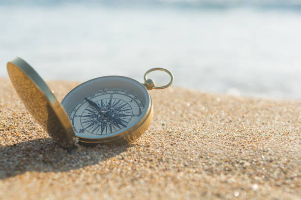 Compass on the golden sand by the sea Compass on the golden sand by the sea antiquities stock pictures, royalty-free photos & images
