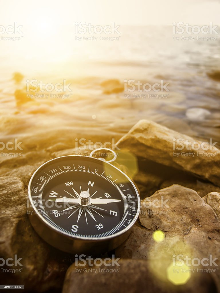 compass on the shore at sunrise stock photo