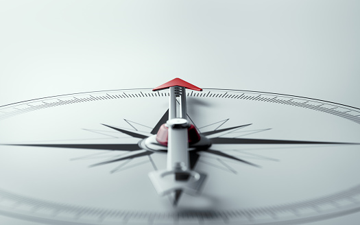 Compass on white background with selective focus. Compass is lit from the upper left corner of composition. Horizontal composition with copy space.