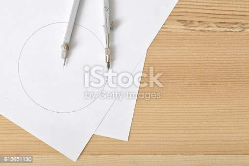 istock Compass on white paper in top view with copy space 613651130
