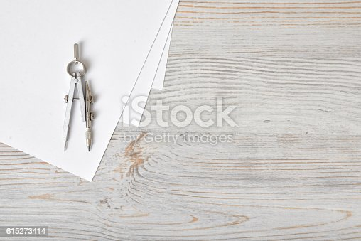 613651130 istock photo Compass on white paper in top view with copy space 615273414
