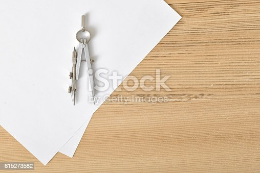 613651130 istock photo Compass on white paper in top view with copy space 615273582