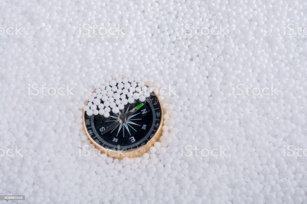 compass on white polystyrene foam balls stock photo