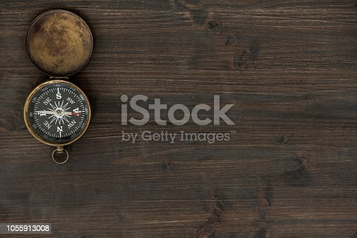 Top view of wooden table with old rusty needle compass.