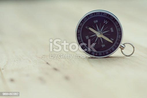 istock Compass on wooden table, journey concept, copy space 988480382