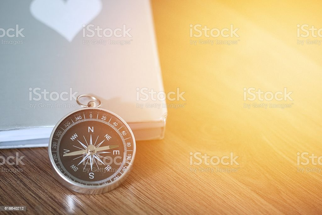 Compass over the book on wooden table stock photo