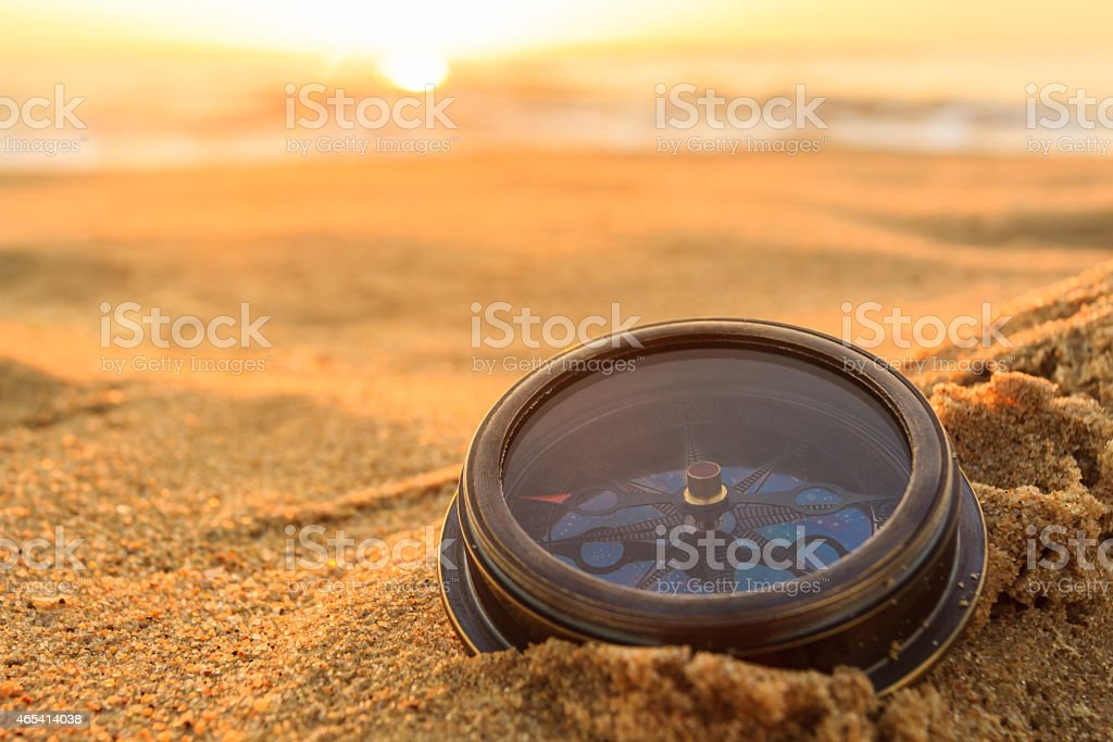 A compass placed on sandy beach stock photo