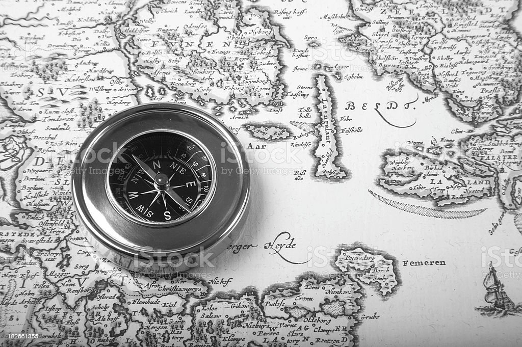 Compass placed upon a old nautical chart in bw stock photo
