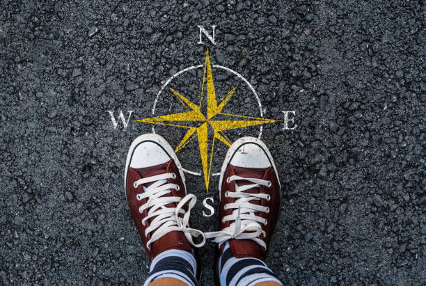 compass sign on road asphalt a man with a shoes standing next to compass sign on road asphalt longitude stock pictures, royalty-free photos & images