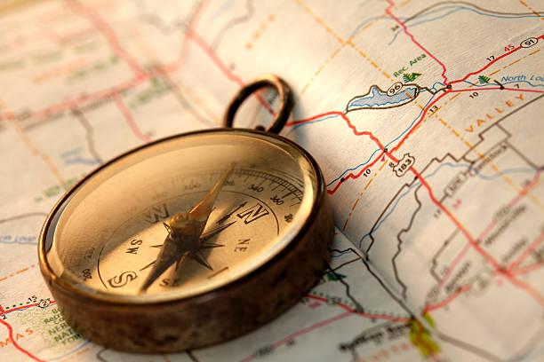 compass sitzt im kreis einer straßenkarte - kompass wanderkarte stock-fotos und bilder