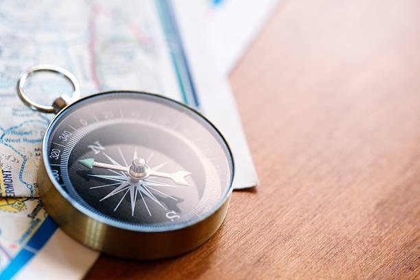kompass sitzen auf gefaltet road karten - kompass wanderkarte stock-fotos und bilder
