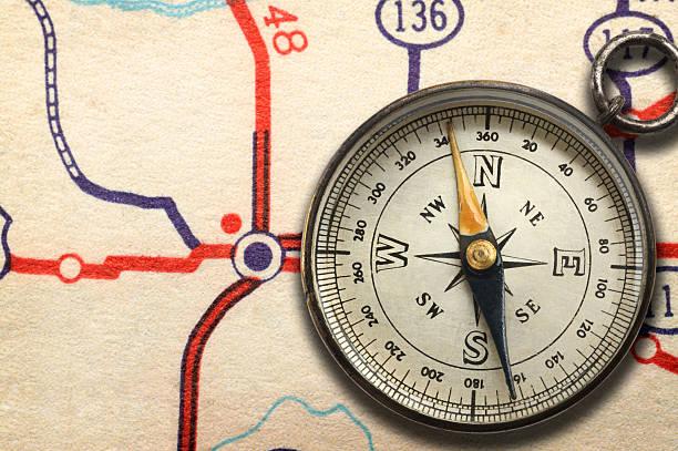 compass sitzt auf landkarte anzeigen highway junction - kompass wanderkarte stock-fotos und bilder