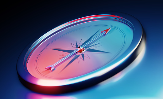 Compass sitting over dark blue metallic background. Horizontal composition with copy space.