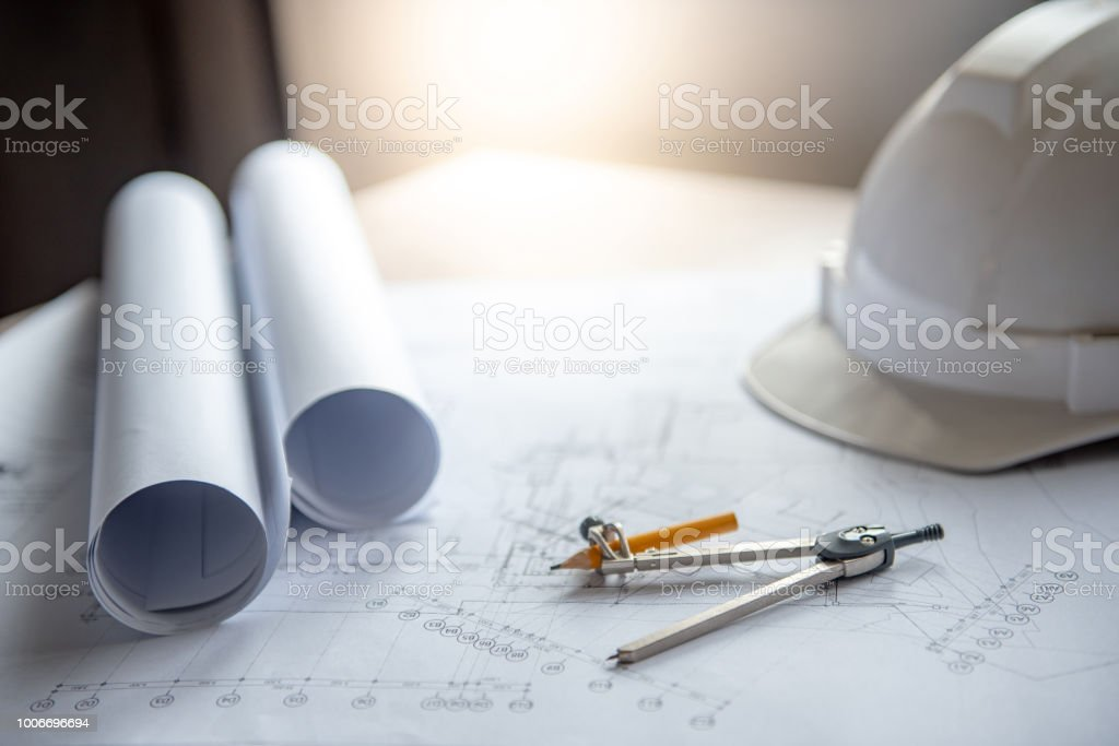 Compass tool and safety helmet on architectural drawing plan of house project, blueprint rolls on working table, Architecture and building construction industry concepts stock photo