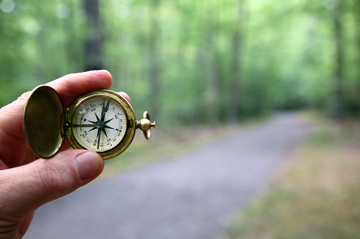 Old brass pocket compass held in fingertips with a blurred gravel path and woods in background.