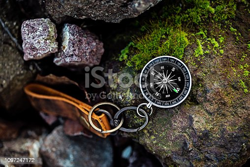 istock Compass with leather keychain on rock natural background Using wallpaper or background travel or navigator image 1097247172