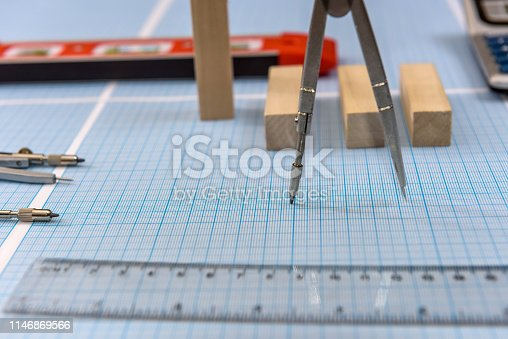 1060723604istockphoto Compass with ruler on millimeter paper close up 1146869566