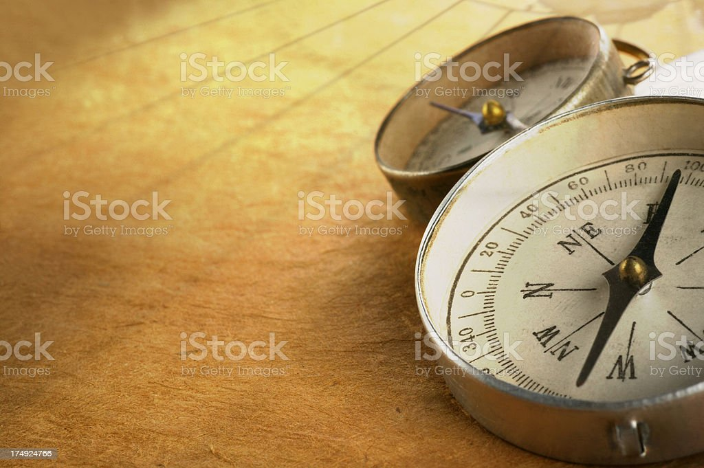 Compasses on golden textured surface royalty-free stock photo