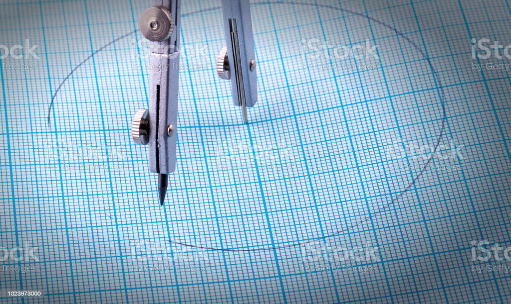 compassescompasses and a circle painted on blue graph paper – zdjęcie