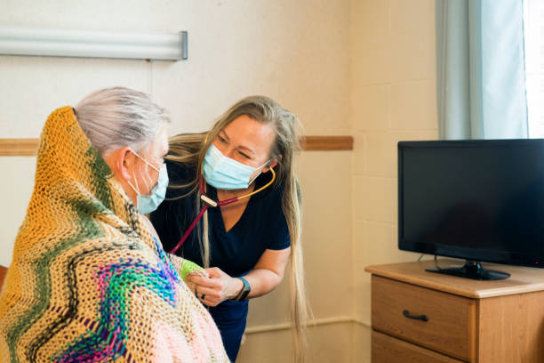 Compassionate nursing care A blond nurse wearing dark navy scrubs and face mask uses her stethoscope to  listen to the lungs of a patient in a medical facility, Midwest, USA inpatient stock pictures, royalty-free photos & images