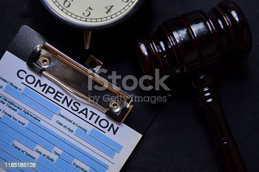 Compensation text on Document and gavel isolated on office desk. Law concept