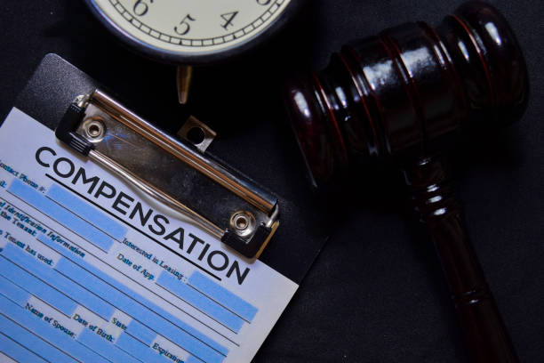Compensation text on Document and gavel isolated on office desk. Law concept stock photo