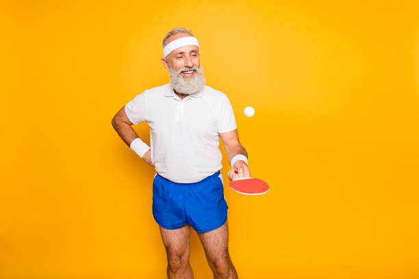 competetive emotional cool active comic grandpa with beaming grin, with table tennis equipment. healthcare, weight loss, bodycare lifestyle, wearing blue sexy shorts, so hot! - tenis stołowy zdjęcia i obrazy z banku zdjęć