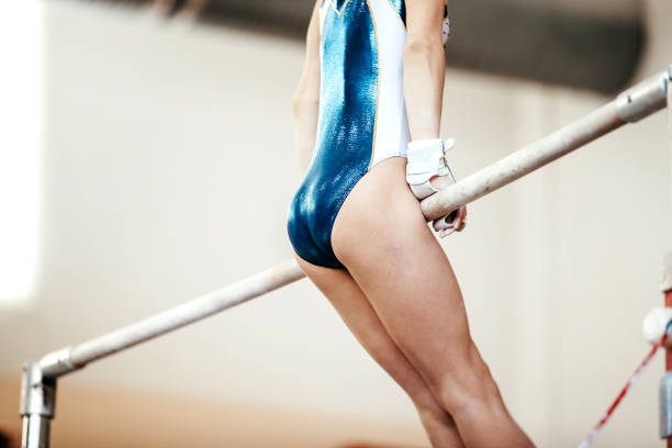 competition in gymnastics exercises on uneven bars girl gymnast stock photo