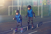 two brothers roller skating in the park, enjoying the competitive game and feeling cheerful.