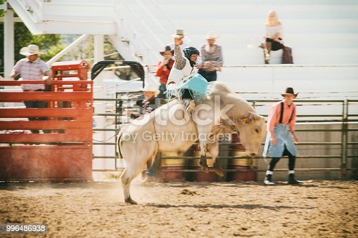 Young men compete in the saddle bronc event at a rodeo. Utah, USA.