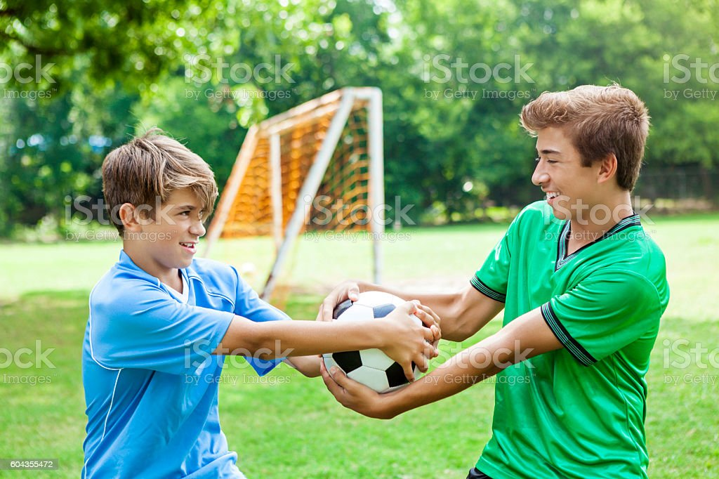 Competitive brothers fight over soccer ball stock photo