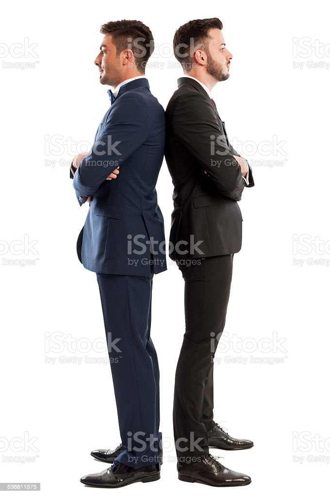 Competitive business men standing back to back stock photo