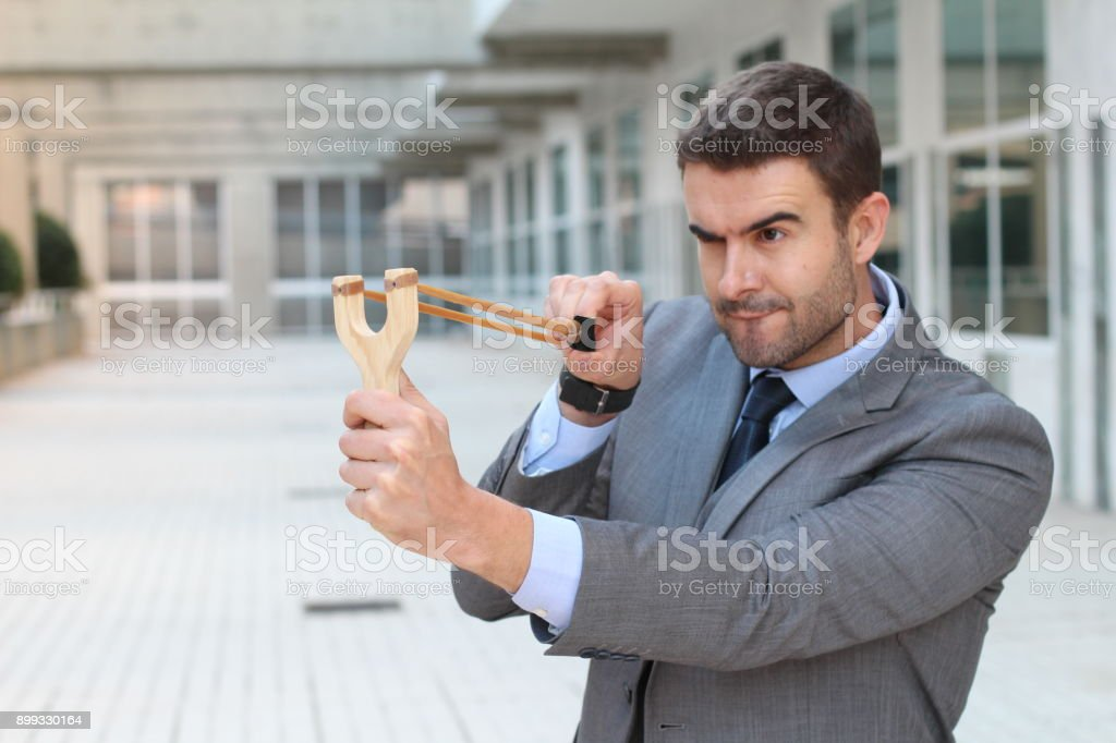Competitive businessman aiming with a slingshot stock photo