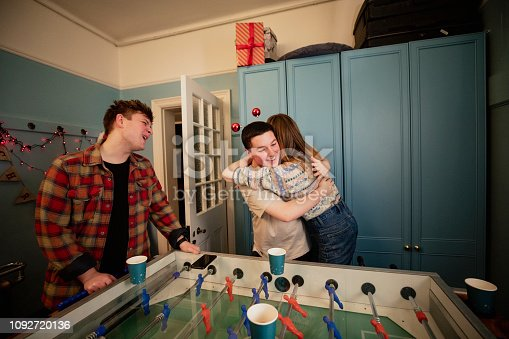 Young adults are playing foosball at a Christmas house party. Two people have won and are hugging in celebration.