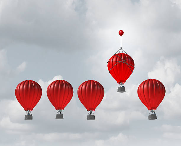 Competitive Edge Competitive edge and business advantage concept as a group of hot air balloons racing to the top but an individualleader with a small balloon attached giving the winning competitor an extra boost to win the competition. improvement stock pictures, royalty-free photos & images
