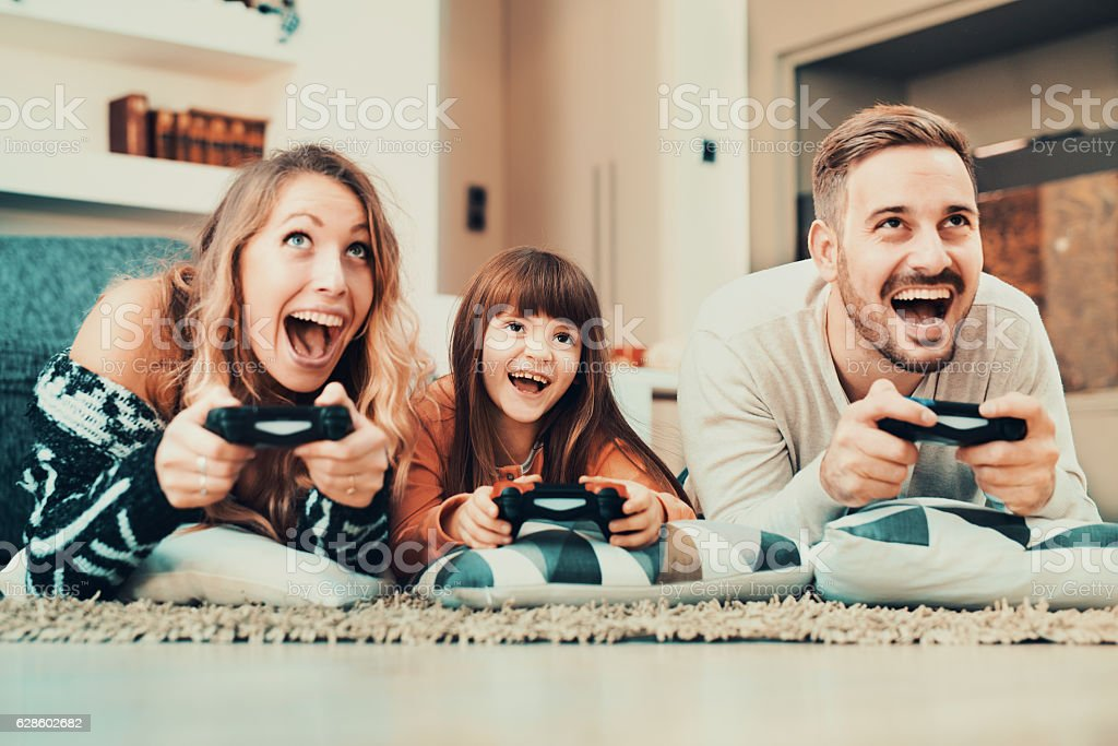 Competitive family playing video games at home stock photo