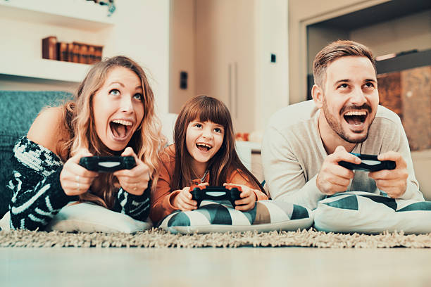 Competitive family playing video games at home - foto de acervo