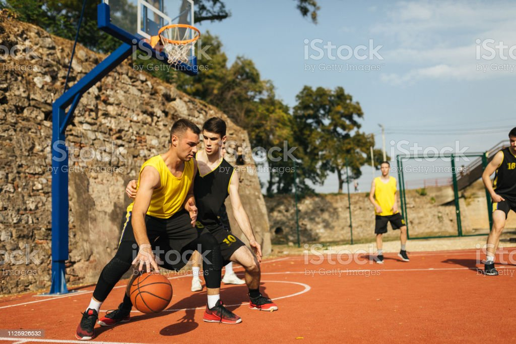 Young player dribbling ball during basketball game outdoor on sunny...