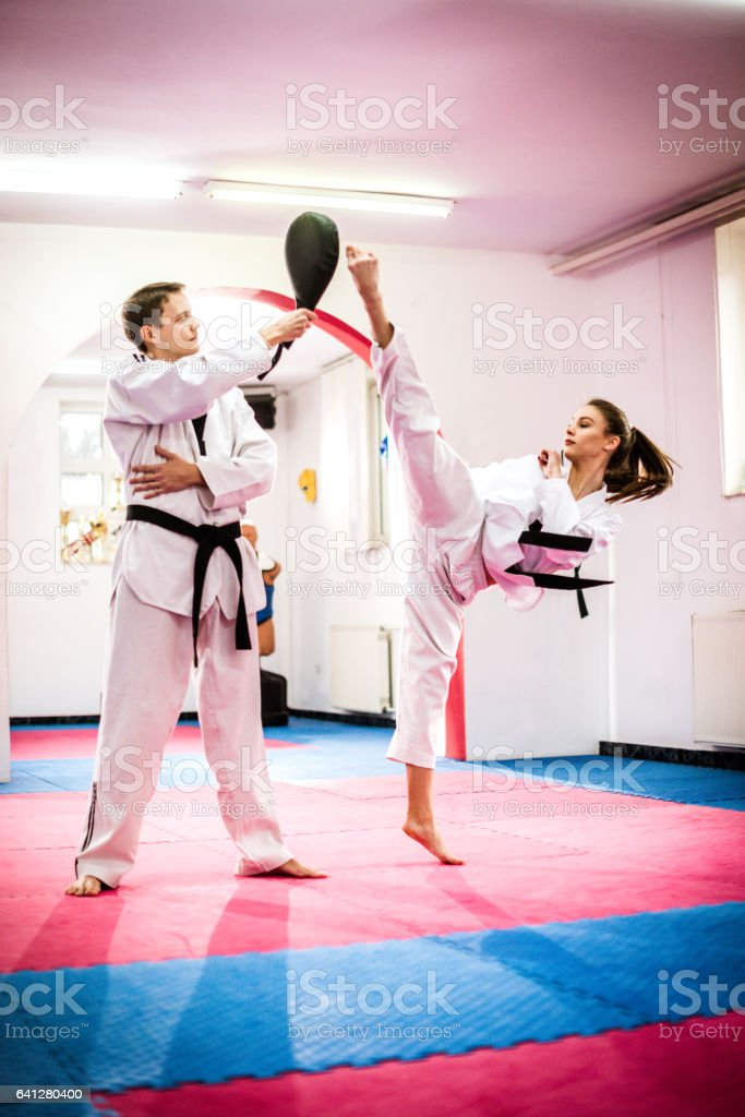 Competitive taekwondo girl on training, round kicking focus mat stock photo