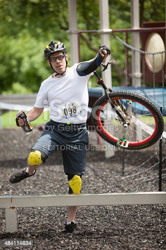 Madison, Wisconsin USA - August 1, 2015: A competitor negotiates an obstacle by carrying his unicycle with one hand while carrying a bag of Tootsie Rolls with his other. Although the Unicycle National Championships are a real thing, not all of the competitors take a serious view of competing in them.