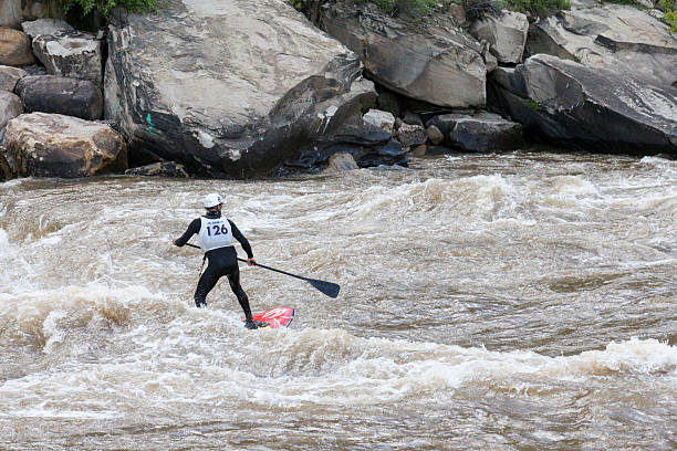 Competitor mid-river during a stand up paddle board surfing competition Durango, Colorado, USA - May 30, 2015: A competitor surfs on a stand up paddle board in a river for a competition during Animas River Days in Durango, Colorado.   animas river stock pictures, royalty-free photos & images