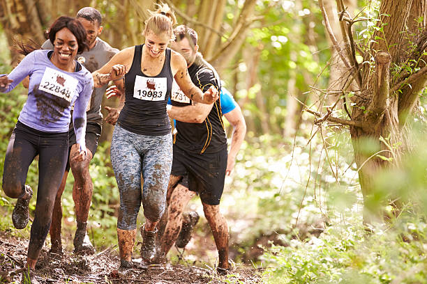 competitors running in a forest at an endurance event - obstacle run stockfoto's en -beelden