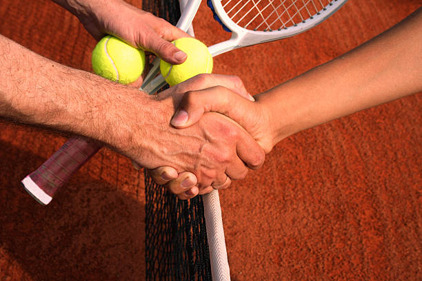 Competitors shake hands before a tennis game stock photo
