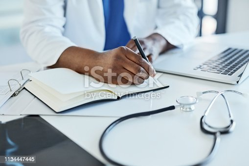 Closeup shot of a doctor using a laptop and making notes in an office
