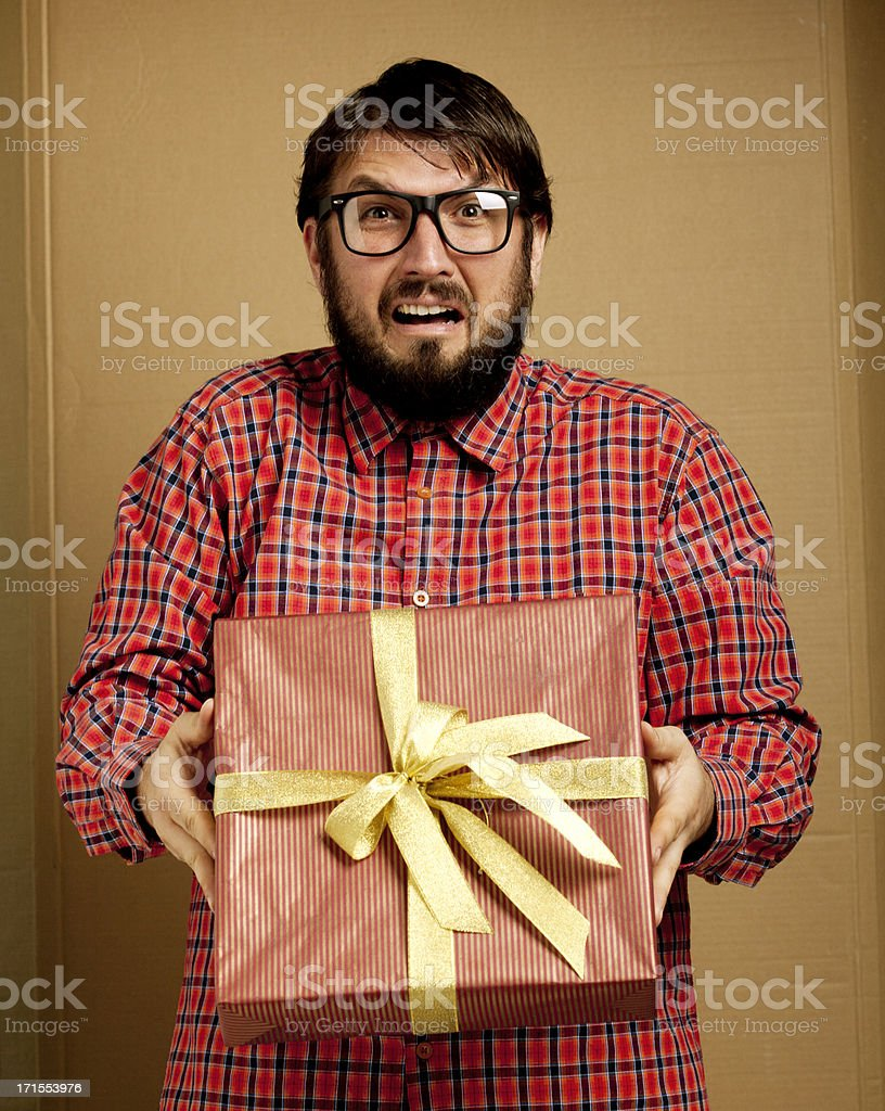Complaining nerd gay holding present royalty-free stock photo
