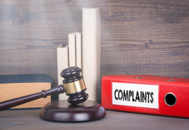Complaints. Wooden gavel and books in background. Law and justice concept stock photo