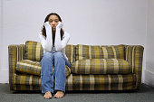 Bored young girl sitting on worn retro loveseatRelated Images: