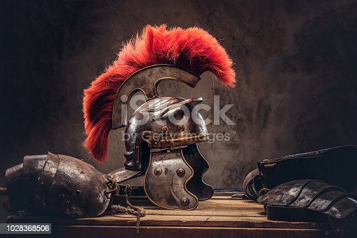 istock Complete combat equipment of the ancient Greek warrior lie on a box of wooden boards. 1028368506